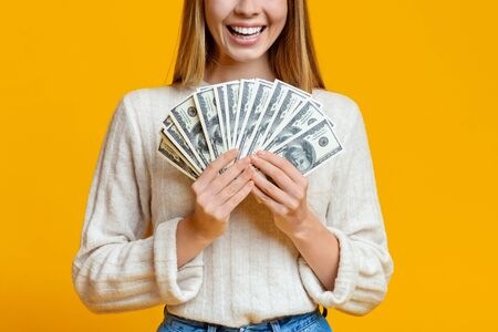 Golden youth. Young girl holding bunch of money and smiling over orange background, closeup Standard-Bild - 132242024