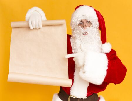 Merry Christmas and Happy New Year. Santa Claus showing on wish list with copy space for text, yellow background Banco de Imagens