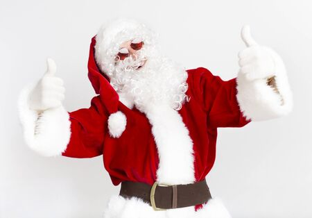 Merry Christmas in warm countries. Modern Santa Claus in sun glasses showing thumbs up on white background