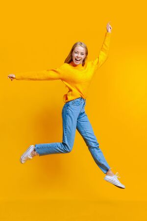 Jumping millennial girl in the air over orange studio background with free space