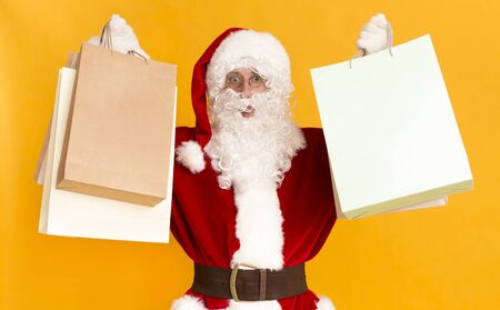 Merry Christmas shopping. Santa Claus holding shopping bags from wow sales day, blank space