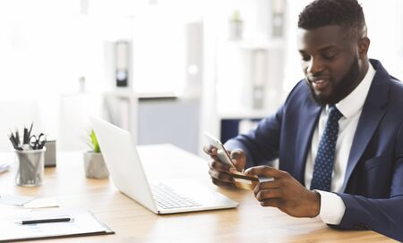 Online banking. African american general manager making online payment on phone at office, holding credit card, free space