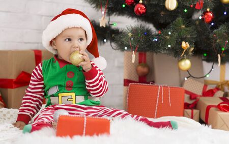 Christmas and teething. Baby biting decoration ball, sitting under Xmas tree, empty space Stock Photo