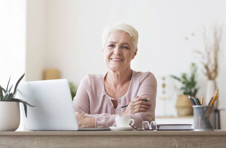Attractive old woman posing at workdesk at home, working with laptop, drinking coffee, copy space