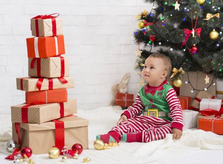 Lots of Christmas gifts. Cute baby looking at high heap of present boxes, sitting near Xmas tree, free space