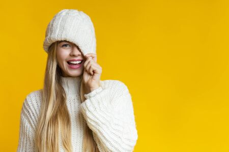 Playful blonde girl covering one eye with knitted hat, copy space