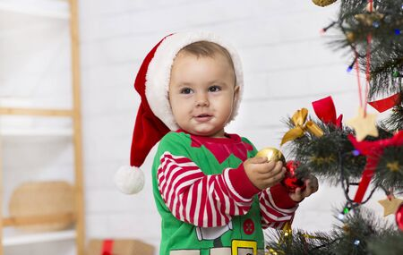 Baby in Santa helper costume decorating Christmas tree at home, empty space
