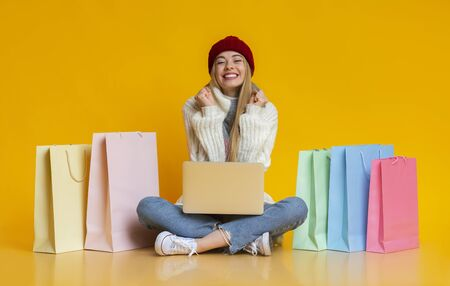 Yes, time for great deals. Girl in knitted hat clenching fists and smiling, sitting on floor with laptop among shopping bags, copy space Standard-Bild - 132244130