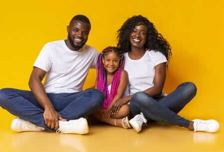 Portrait of joyful african family with cute little daughter sitting on floor and smiling at camera over yellow studio background. Stock Photo