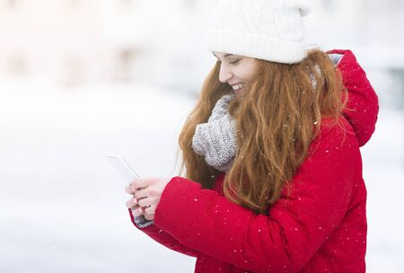 Side view of young woman using phone, walking by winter city, sharing photos with friends, copy space Imagens
