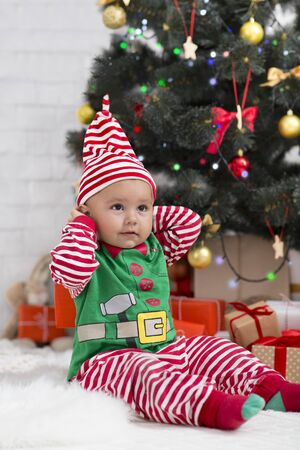 Christmas elf. Cute baby sitting under Xmas tree in holiday costume, empty space