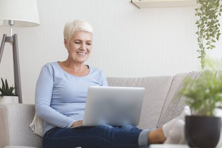 Smiling old woman working from home, typing email on laptop, sitting on sofa, copy space