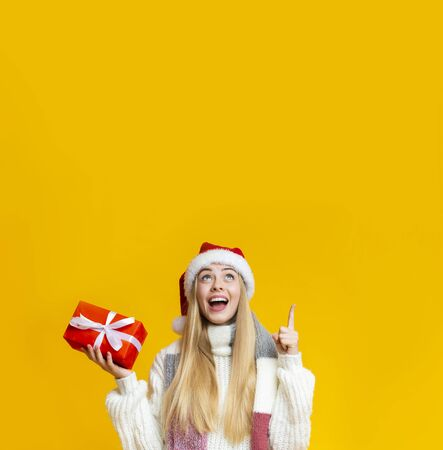 Time to buy christmas gifts. Excited girl in santa hat with gift box pointing at copy space