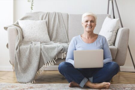 Happy active old woman sitting on floor at home and using laptop, copy space Stockfoto