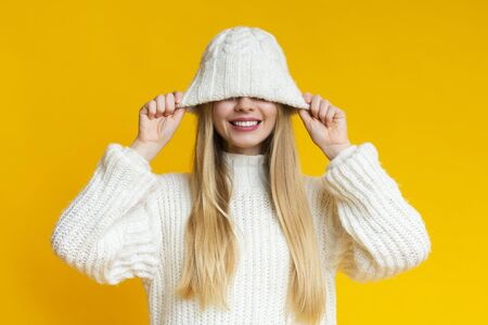 Playful blonde woman pulling down woollen white hat and smiling, yellow background