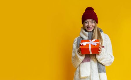 Portrait of smiling girl in red warm hat holding festive gift, winter holidays coming, panorama with copy space