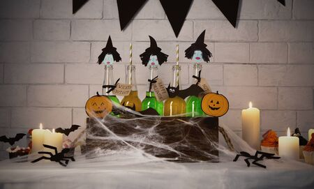 Halloween nightmare. Cute witches with green bodies inside box with spider web, bricks wall background, panorama