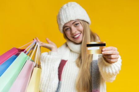 Happy young woman in white hat recommending credit card, posing with colorful shopping bags and smiling at camera, yellow background
