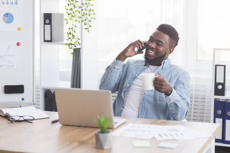 Cheerful black office worker talking on phone, laughing and drinking coffee at workplace, copy space Stock Photo