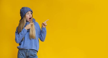 Stunned blonde woman looking and pointing at copy space, shocked offer, panorama Stock Photo