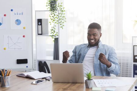 Yes, I did it. Ecstatic African American Worker Looking At Laptop Screen Rejoicing Business Success At Workplace In Modern Office