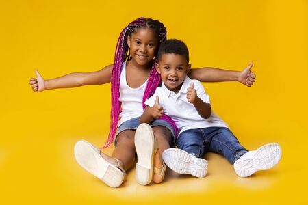 Kids recommend. Adorable little black sister and brother showing thumbs up while sitting on floor on yellow studio background.