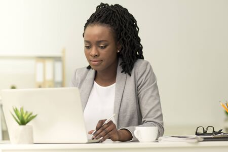 Serious Black Businesswoman Working On Laptop In Modern Office. Business Lifestyle Concept Foto de archivo