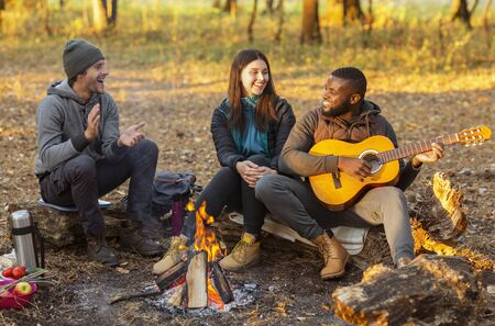 Happy international group of hikers sitting around campfire and singing, autumn forest background