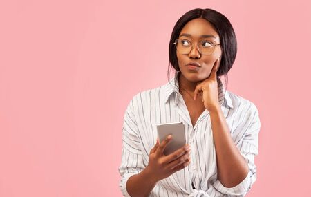 Thoughtful African American Girl Using Smartphone Thinking About Something Standing Over Pink Studio Background. Free Space 스톡 콘텐츠