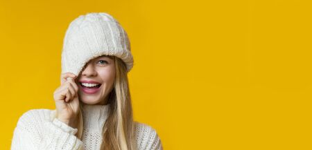 Offer, deal, sale concept. Pretty girl in winter hat flirting over yellow studio background, panorama with copy space
