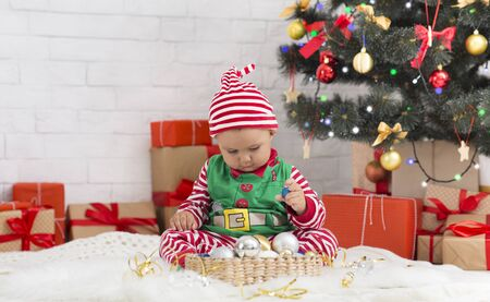 Sweet Santa helper playing with holiday decorations under Christmas tree, free space Stock Photo