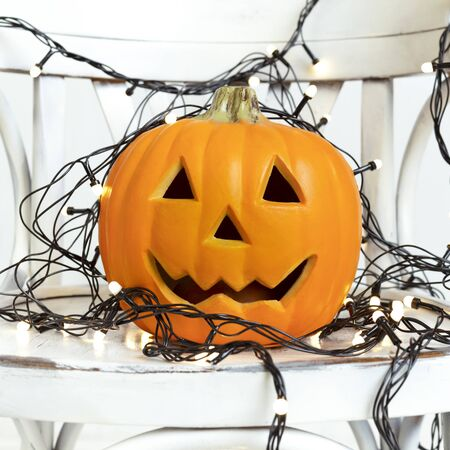 Smiling Halloween pumpkin with cutting out eyes and holiday garland on white background Stock fotó
