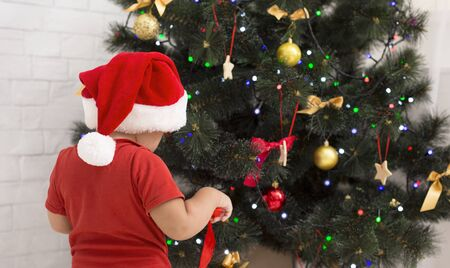 Christmas time. Baby in Santa het preparing for holidays, decorating Xmas tree at home, free space Stock Photo