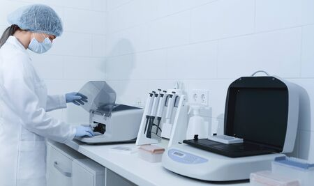 Young woman working in modern laboratory and using analyzer machine, panorama, copy space Stok Fotoğraf