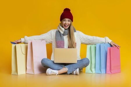 Happy girl in warm clothes with laptop on her knees putting hands on shopping bags, season of big discounts, copy space