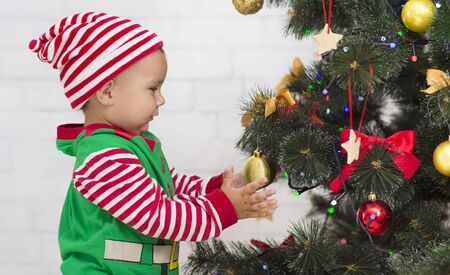Adorable Santa helper decorating Christmas tree at home, side view