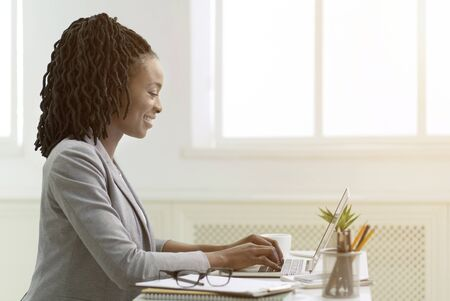 African American Employee Woman Working On Laptop Sitting In Modern Office. Side View