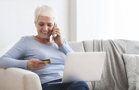 Old lady making purchases online, checking her credit card number, copy space