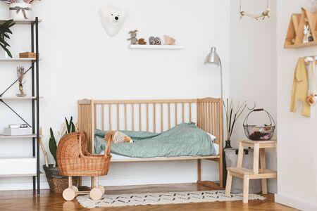 Baby Bedroom Interior with Cozy Wooden Bed, Wicker Stroller and Rack In Scandinavian Style