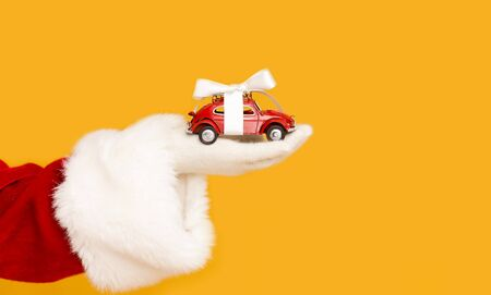 Christmas sale. Santa Claus holding modern car with bow in hand over orange background, copy space