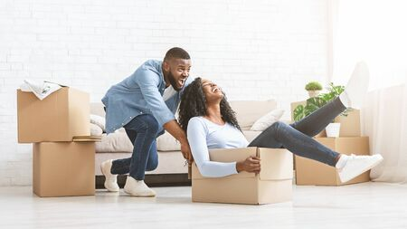 Young african american playful man pushing packing box with his happy woman in it, having fun while moving in new house, panorama with copy space Stock Photo