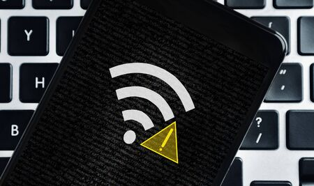 Wireless connection error. Smartphone with wifi icon and exclamation mark on screen over laptop keyboard background, closeup