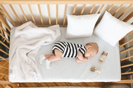 Top view of cute infant baby sleeping on his side in wooden cot Фото со стока