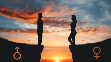 Gender gap. Silhouettes of man and woman standing on rock tops with gender signs. Reklamní fotografie