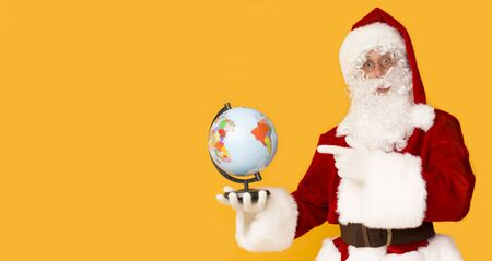 Santa Claus holding globe and showing North Pole with finger, panorama, copy space