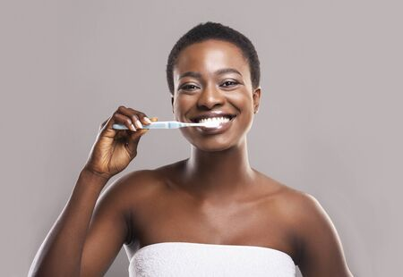 Oral hygiene concept. Portrait of beautiful african american woman brushing white healthy teeth to prevent caries, gray background with copy space