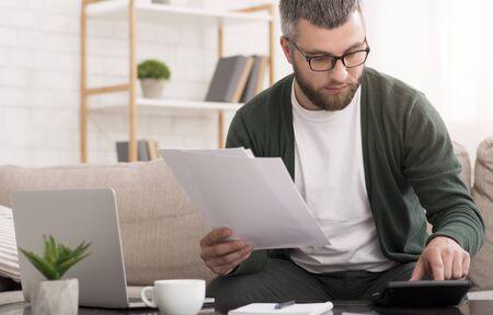 Oszczędności, finanse, koncepcja gospodarki, mężczyzna w średnim wieku z kalkulatorem liczącym pieniądze, trzymając papiery, wnętrze domu, miejsce na kopię