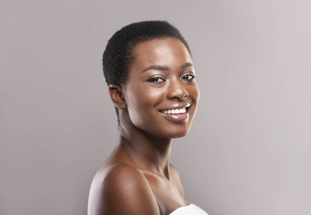 Schönheits- und Körperpflegekonzept. Nahaufnahmeporträt der jungen schönen afroamerikanischen Frau mit dem kurzen Haar, das in Badetuch gewickelt wird, grauer Hintergrund Standard-Bild