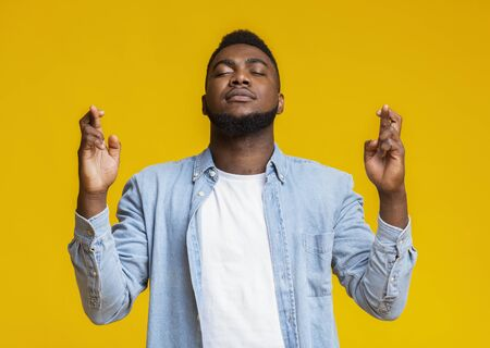 Gekoesterde wens. Doordachte Afro-Amerikaanse man bidden met gekruiste vingers en gesloten ogen, hopend op fortuin en veel geluk