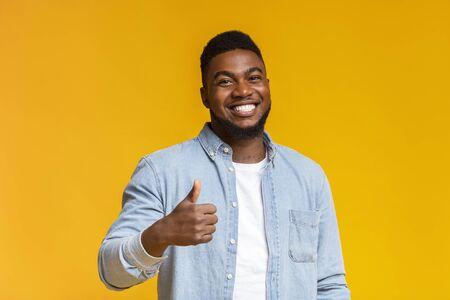 Richtige Wahl. Porträt eines lächelnden, blachen Kerls, der Daumen vor der Kamera über gelbem Hintergrund mit freiem Speicherplatz zeigt Standard-Bild